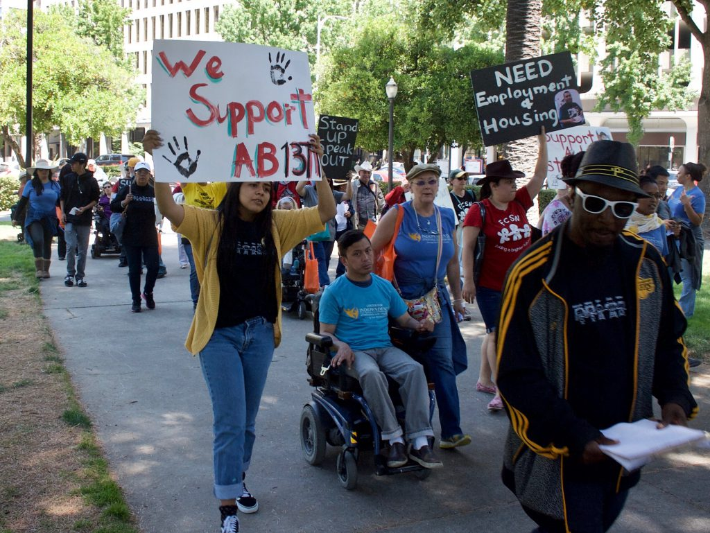 A photo of people making their way towards the capitol holding various signs.
